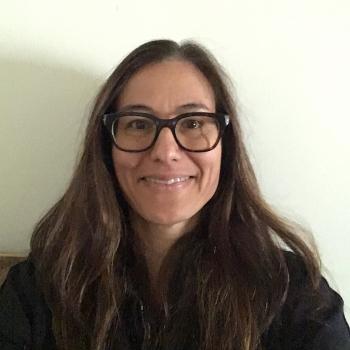 portrait of Camilla Fojas, director of ASU's School of Social Transformation. Fojas has long dark hair, is smiling and wearing glasses