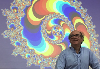 man in front of screen with a fractal on it