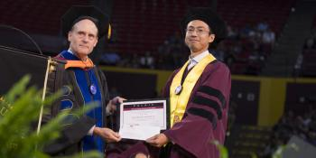 "Photo of Steve Phillips and Zhengshan ""Jason"" Yu holding a plaque."