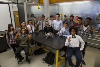 "A group of ethnically diverse students gather around a table, displaying the ""pitchfork,"" Arizona State University's signature hand gesture. On the table sits a LEGO robot, and the students are surrounded by tools and equipment."