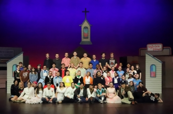 group photo of high school theater students on stage