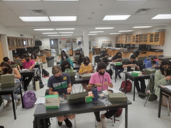 Students in masks doing a STEM project