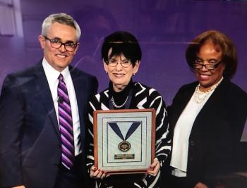 three people posing for photo, with woman in middle holding award