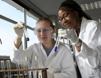 Two women wearing protective lab gear hold and examine test tubes.