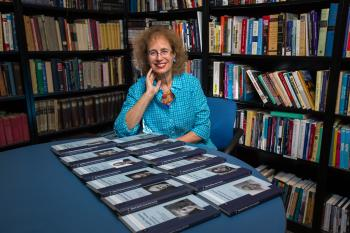 woman sitting in office with volume of books on table