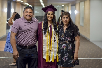 A young woman poses with her parents in her graduation regalia at the Hispanic Mother Daughter Program graduation at ASU