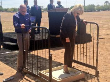 AZ Governor Jan Brewer steps in cement as GoDaddy CEO Blake Irving looks on.