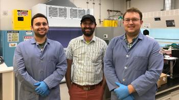 Three people pose in a lab