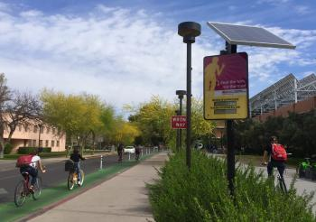 Bicyclists ride past the bike counter at College and Apache