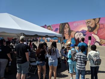 Crowd sits and stands in front of stage set up in front of mural