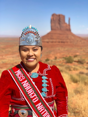 ASU alumna Shaandiin Parrish wearing a crown standing in front of a desert backdrop