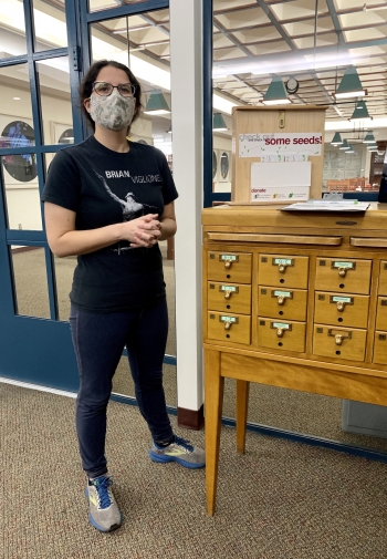Christina Sullivan stands next to the card catalog housing the seed library