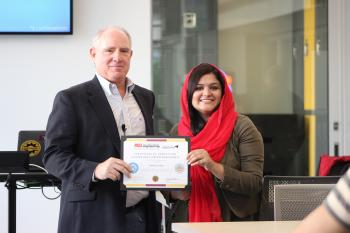 Kenneth Mulligan, professor for the U.S.-Pakistan Centers for Advanced Studies in Energy, presents Pakistani exchange scholar Nafeesa Irshad with her certificate of completion for the entrepreneurship portion of the program. Photographer: Erika Gronek/ASU