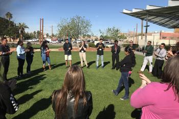 Parks and recreation professionals and students stand in a circle on the grass for an activity-based workshop