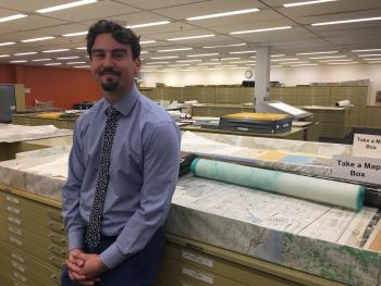 director of Map and Geospatial Hub standing in front of old maps
