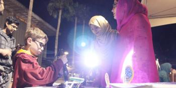 Above: Hira Rehman (in pink) and Asma Shamim (in gold) demonstrate the power of photovoltaics with members of the Tempe community during Night of the Open Door. Photographer Erika Gronek/ASU
