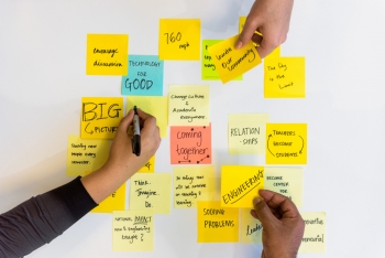 Three hands write ideas down and place sticky notes next to each other on a table