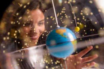 student smiling and looking at a globe