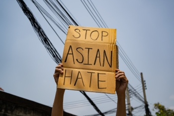 Hands hold up a cardboard sign that says Stop Asian Hate