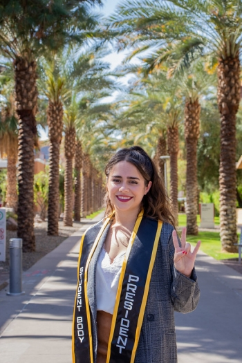 Jacqueline Palmer on palm walk in a stole that says Student Body President