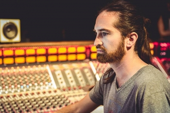 International music engineer Jorge Costa Palazuelos sitting in a music studio with a mixing board in the background.