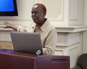 Beatrice A. Bunyasi of Kenyatta University speaks during a symposium at ASU in April. She has orange hair and is wearing a button-up shirt. She stands at a podium with a laptop sitting on it.