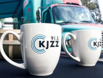Two white coffee mugs with the KJZZ logo on them.