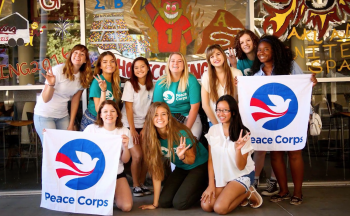 group photo of students holding peace corps signs