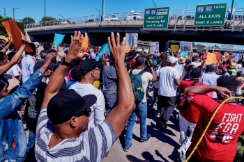 Black Lives Matter protesters carrying signs walk under a freeway overpass in Chicago