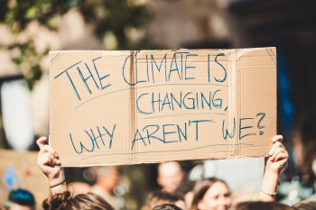 """A cardboard sign that reads """"THE CLIMATE IS CHANGING, WHY AREN'T WE?"""""""