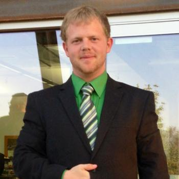 blonde haired Bradley Baker wearing black suit and green shirt and tie standing