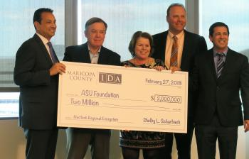 group of 5 people holding giant check