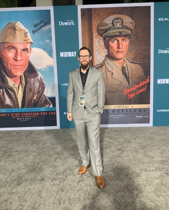 man standing in front of movie posters