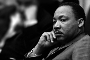 A black-and-white photo of Martin Luther King Jr. sitting and thinking.