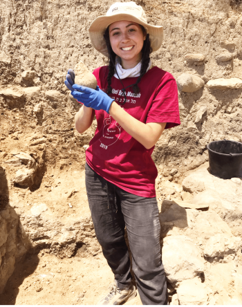 Molly Corr holding a vessel from the excavation site Tel Abel Beth Maacah in Northern Israel.