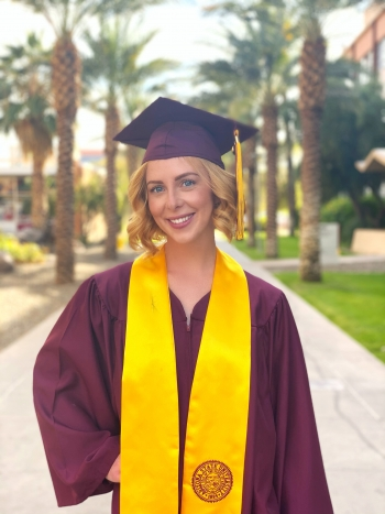 Molly Joy Lode stands in her cap and gown on ASU Tempe campus
