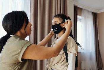 A mom placing a face mask on a child