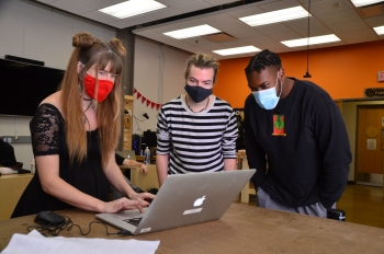 Photo of Lauren Copley and students working together during a workshop event
