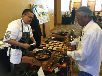 Chef Nephi Craig chats with attendee at RED INK Sustainability Dinner, April 22, 2017. / Photo by Henry Quintero