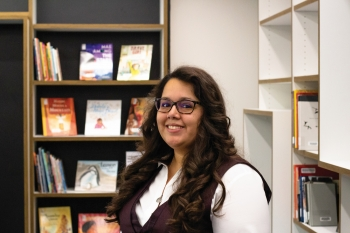 Nancy Godoy poses for a photo in front of the community driven collections in Hayden Library