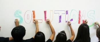 "Students write the word ""solutions"" on a whiteboard in different colored markers."