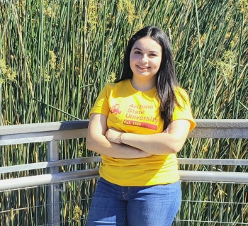 Odalis Amaya Amaya wears blue jeans and a yellow ASU T-shirt. Her arms are crossed in front of her. She is smiling and has long dark wavy hair. She is standing in front of a gray fence in front of tall grass.