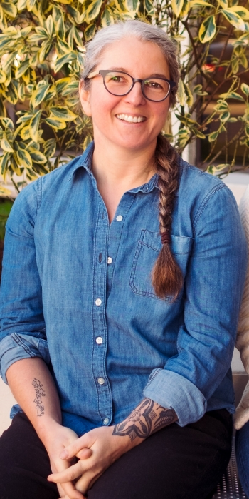 Sabrina Oesterle, a light skinned woman with a long gray and brown braid and glasses, smiles at the camera wearing a blue denim shirt with wrist tattoos showing