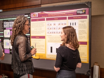 two women speaking in front of a research poster