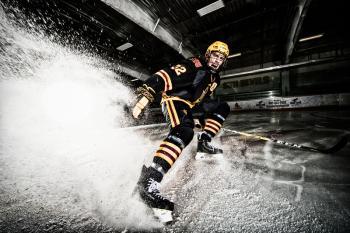 hockey player spraying ice into camera