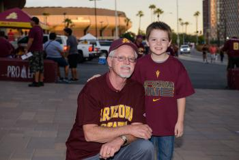 ASU alumnus Michael Peddecord and his grandson Ryan attend an ASU football game.