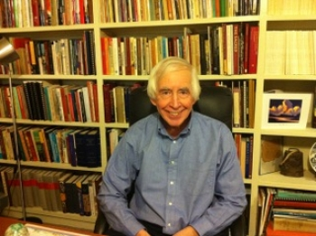 Professor Peter James Iverson smiles at the camera while sitting in front of a full bookcase