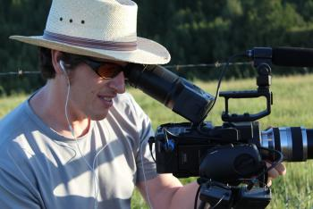 Peter Byck wearing a hat and sunglasses outside looking into video camera