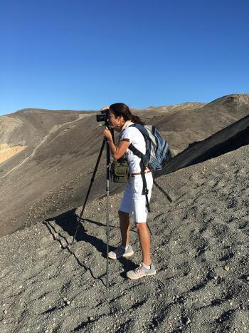 A dark-haired woman in white shorts and a white t shirt stands at a tripod on a gravel hill, taking a photograph
