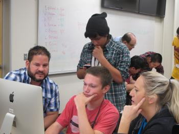 High school students and teachers work around a computer.